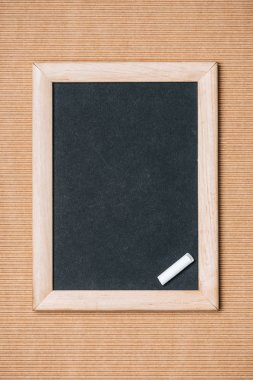 Top view of empty blackboard and piece of chalk on brown background stock vector