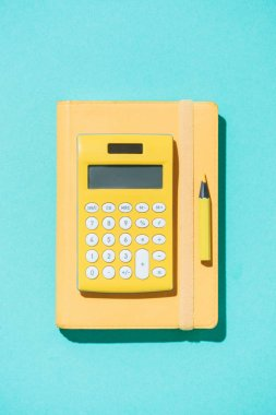 top view of arrangement of calculator, pencil and notebook on blue backdrop