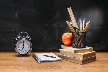 close up view of fresh apple, clock, notebook, pencils and books on wooden tabletop with empty blackboard behind