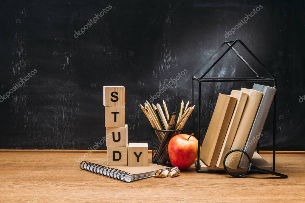 Close up view of study inscription made of wooden blocks, notebook, fresh apple and books on surface with empty blackboard behind stock vector