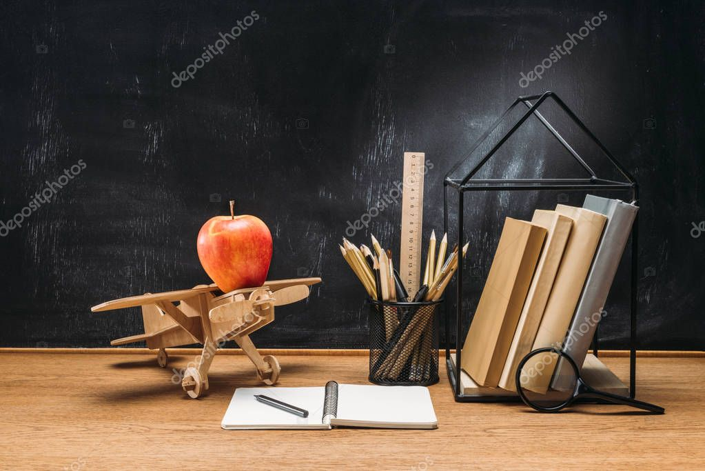 Close up view of apple on wooden toy plane, notebook, books and pencils on tabletop with empty blackboard behind stock vector
