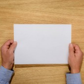 Fotografie ořízne obraz člověka drží nad dřevěný stůl prázdný dokument white paper