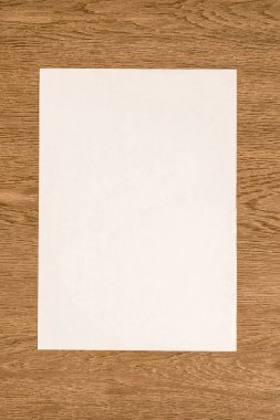 view from above of blank white paper on wooden table