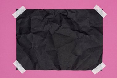 top view of blank crumpled black paper on pink
