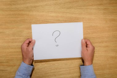 cropped image of man holding paper with question mark over wooden table
