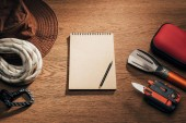 Fotografie top view of blank notepad with pencil and trekking and hiking items on wooden table