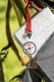 Fotografie close-up view of compass hanging on backpack and map
