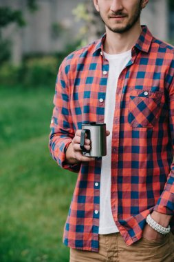 cropped shot of young man in checkered shirt holding mug