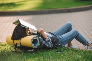girl holding map on face while lying with backpack on grass