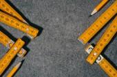 Fotografia vista superiore del metro pieghevole e matite su superficie grigia
