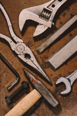 top view of old shabby mechanical tools on brown surface
