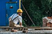 a fiatal építőipari munkás pihent a raklap hardhat és védő googles hátsó nézet
