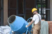 Fotografie construction worker in hardhat and protective googles working with concrete mixer on construction site