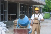 Fotografie young builder in hardhat and protective googles standing with shovel near concrete mixer at construction site