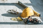 close up view of hardhat, spirit level, drill and protective gloves with googles at construction site