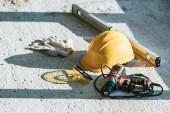 Fotografie zblízka pohled bezpečnostní přilba, vodováha, vrtačka a ochranné rukavice s brýle na staveništi