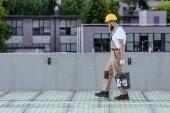 boční pohled na tvůrce v ochrannou přilbu a brýle nesoucí kbelík cementu na staveništi