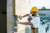 Fotografia Costruttore in elmetto protettivo e googles facendo isolamento della parete al cantiere