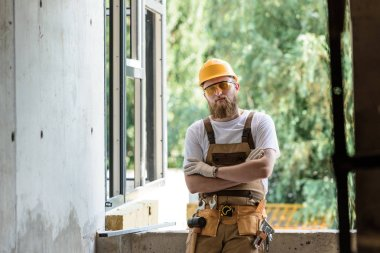 smiling builder in protective googles and hardhat standing with crossed arms at construction site