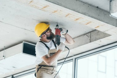 low angle view of builder in protective googles and hardhat working with drill at construction site