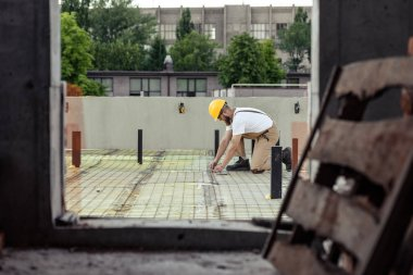 selective focus of builder in protective googles and hardhat working at construction site