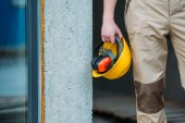 Fotografie cropped image of builder in uniform holding construction headphones and protective helmet