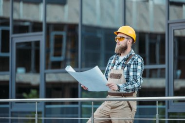 young construction worker in protective googles and hardhat looking at blueprint