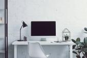 počítač, stůl, židle a rostliny v moderní kanceláři