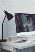 Fotografie počítač a kávu v pohárek na stůl v moderním prostoru