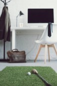 Fotografie golf club and ball on green grass carpet in modern workplace