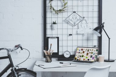 laptop with loaded pinterest page on table in modern office