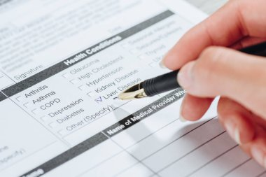 cropped image of woman marking liver disease in medical questionary, world hepatitis day concept