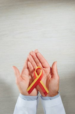cropped image of female doctor holding ribbon, world hepatitis day concept