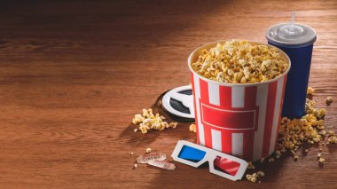 close up view of paper bucket with popcorn, soda drink, 3d glasses on wooden tabletop