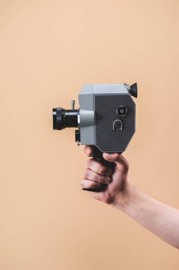 cropped shot of man holding retro camera in hand isolated on beige