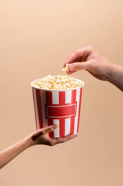 cropped shot of male and female hands with disposable bucket with popcorn isolated on beige