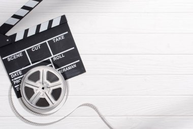 flat lay with clapper board and filmstrips on white wooden tabletop