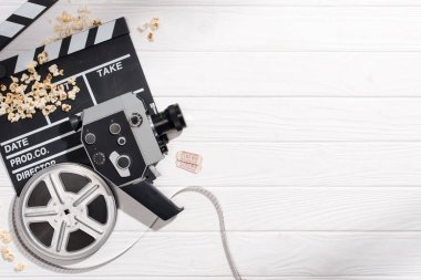 flat lay with clapper board, filmstrips, retro camera and cinema tickets arranged on white wooden surface