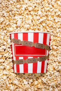 flat lay with disposable bucket, crunchy popcorn and retro cinema tickets