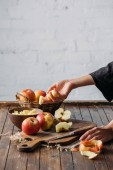 Fotografia ritagliata colpo della donna con pezzi di mela in mano e mele fresche sul tagliere il piano in legno