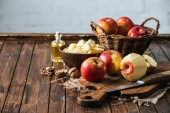Fotografie close up view of bottle of juice, fresh apples on cutting board, hazelnuts and knife on wooden surface