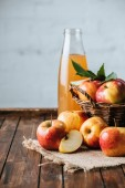 Fotografie close up view of glass bottle of apple juice and apples in basket on wooden tabletop
