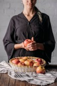 Fényképek partial view of woman with apple and basket full of fresh apples on wooden tabletop with linen