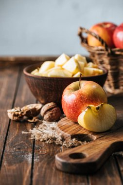 close up view of cut and wholesome apples on cutting board on dark wooden surface