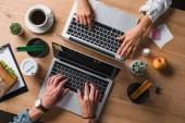 Schnappschuss von Geschäftsleuten, die am Arbeitsplatz mit Laptops arbeiten