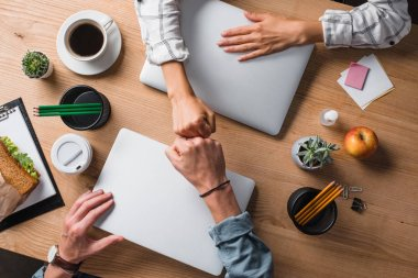 cropped shot of businesspeople doing fists gesture at workplace