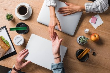 cropped shot of businesspeople shaking hands at workplace