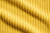 Fényképek full frame image of wavy yellow woolen fabric background