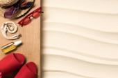 Fotografie plochý ležela s ženskou červené doplňky pro odpočinek na pláži v písku