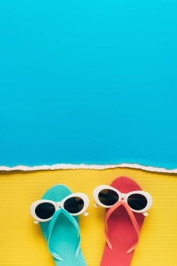 top view of blue and pink flip flops with sunglasses on yellow and blue paper background